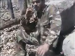 Soldier strokes dick in forest